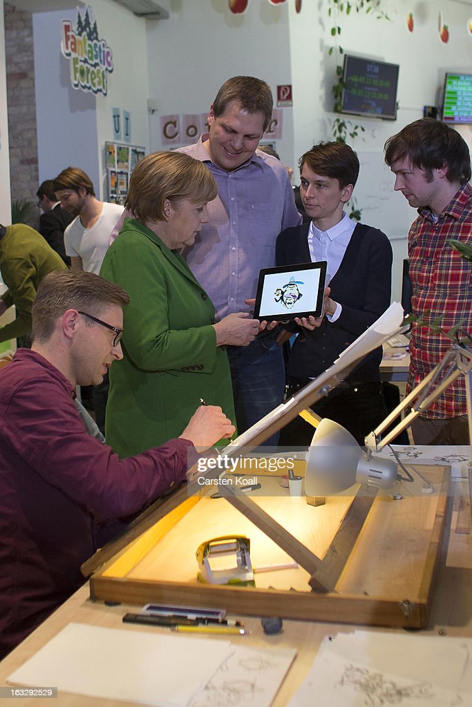 Stephanie Kaiser (2nd R), studio head, explains German Chancellor Angela Merkel (2nd L) a game, during guided tour by the general manager Jens Begemann (C) in the Wooga company, which makes social games for smartphones and tablets, on March 7, 2013 in Berlin, Germany. Berlin has drawn a significant number of startup companies in recent years, many of which are drawn by the city's hip reputation and its comparatively low cost of living.