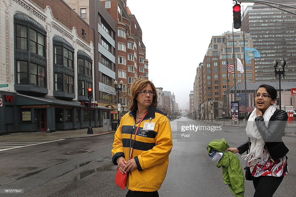 Stephanie Prashad (R), 22, is the first person escorted back onto Boylston Street through the Hynes, by city worker Christine Sullivan, April 23, 2013 in Boston, Massachusetts. The city conducted a final cleanup of Boylston Street and started opening the street to residents and business owners.