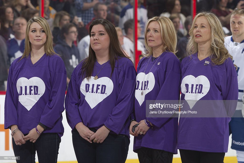 Stephanie Richardson (second from right), wife of Luke Richardson (not shown), a former Ottawa Senators player, looks on a centre ice following a ceremonial puck drop in support of Do It For Daron (D.I.F.D.) night, during the singing of the national anthem prior to an NHL game against the Toronto Maple Leafs, at Scotiabank Place on February 23, 2013 in Ottawa, Ontario, Canada.