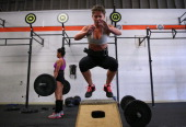 Stephanie St Claire does a box jump during a CrossFit workout at Ross Valley CrossFit on March 14 2014 in San Anselmo California CrossFit a high...