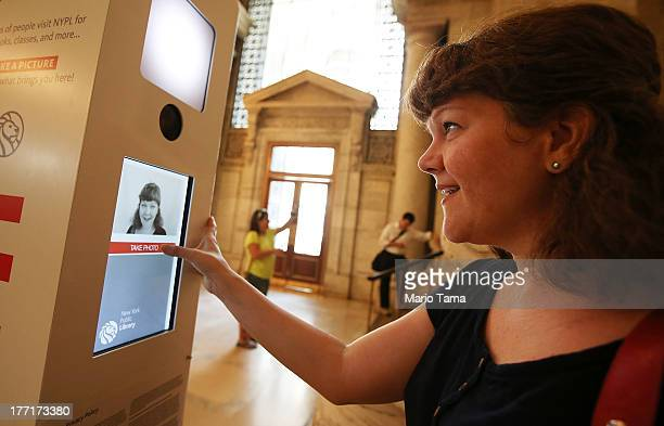 Stephanie Thompson takes a 'selfie' at a new photobooth in the New York Public Library on August 21 2013 in New York City Visitors are invited to...