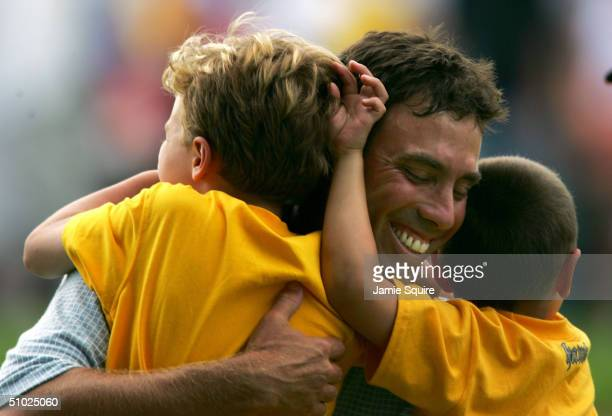Stephen Ames of Canada recieves a hug from sons Justin and Ryan on the 18th green after winning the Cialis Western Open on July 4 2004 at Cog Hill...