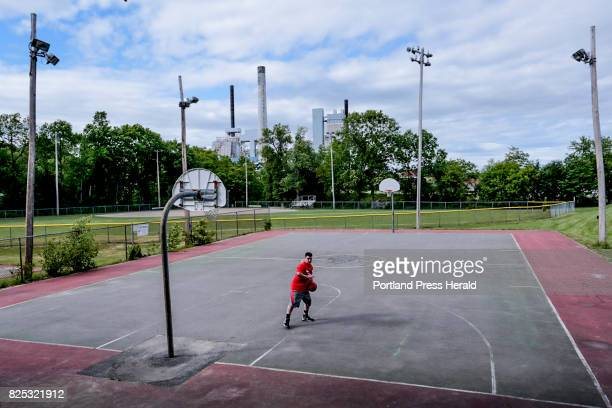 Stephen Barber backs down an imaginary post defender while playing basketball with himself on the courts in Westbrook the Sappi paper mill looming in...