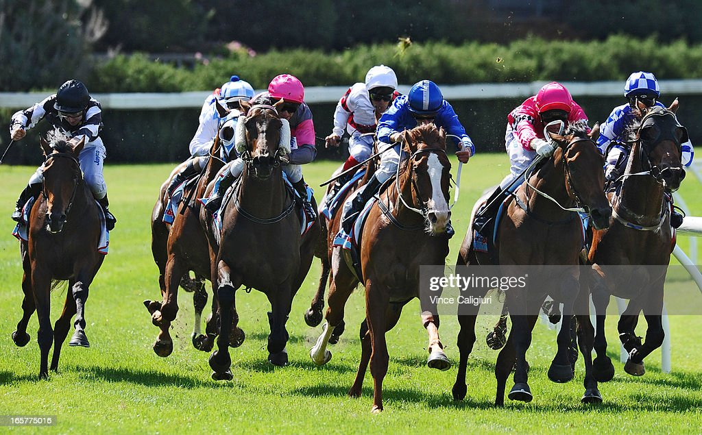 Stephen Baster riding Gold Medals (2nd from L) swoops around the home turn before winning Zouki Handicap during Melbourne racing at Moonee Valley Racecourse on April 6, 2013 in Melbourne, Australia.