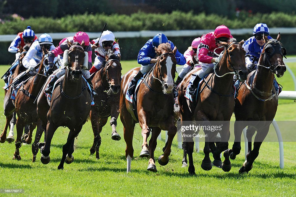 Stephen Baster riding Gold Medals (L) swoops around the home turn before winning Zouki Handicap during Melbourne racing at Moonee Valley Racecourse on April 6, 2013 in Melbourne, Australia.