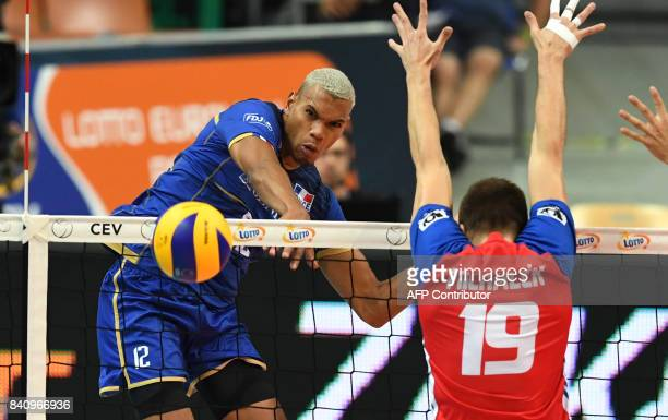 Stephen Boyer of France spikes the ball against Petr Michalek of the Czech Republic during the playoff phase match between France and Czech Republic...