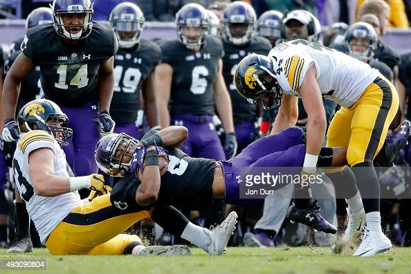 Stephen Buckley of the Northwestern Wildcats is tackled by Josey Jewell of the Iowa Hawkeyes and Ben Niemann during the first quarter at Ryan Field...