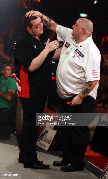 Stephen Bunton is congratulated by Robbie Green after winning their semifinal during the BDO World Championships at the Lakeside Complex Surrey
