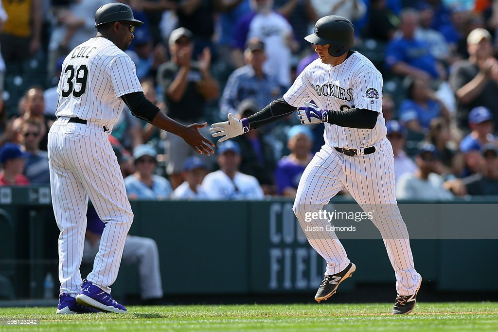 Stephen Cardullo #65 of the Colorado Rockies celebrates his first career Major League home run with Third Base Coach Stu Cole of the Colorado Rockies during the seventh inning against the Los Angeles Dodgers at Coors Field on August 31, 2016 in Denver, Colorado.