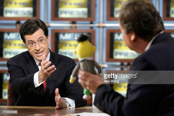 Stephen Colbert host of 'The Colbert Report' speaks as moderator Tim Russert holds up the Sesame Street figure Bert during a taping of 'Meet the...