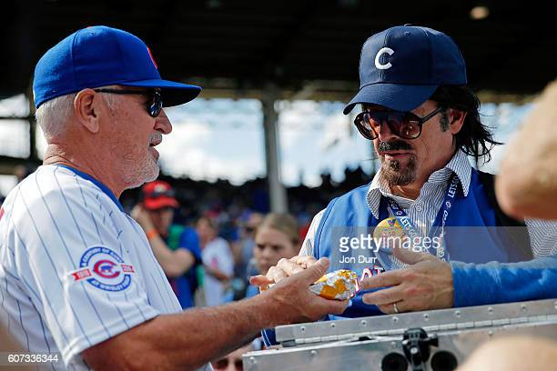Stephen Colbert playing the role of Wrigley Field hot dog vendor Donny Franks hands a hot dog to manager Joe Maddon of the Chicago Cubs during...