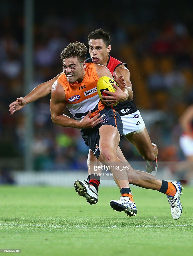 Stephen Coniglio of the Giants is tackled by Mark Baguley of the Bombers during the round three of the NAB Cup AFL match between the Greater Western Sydney Giants and the Essendon Bombers at Manuka Oval on March 8, 2013 in Canberra, Australia.