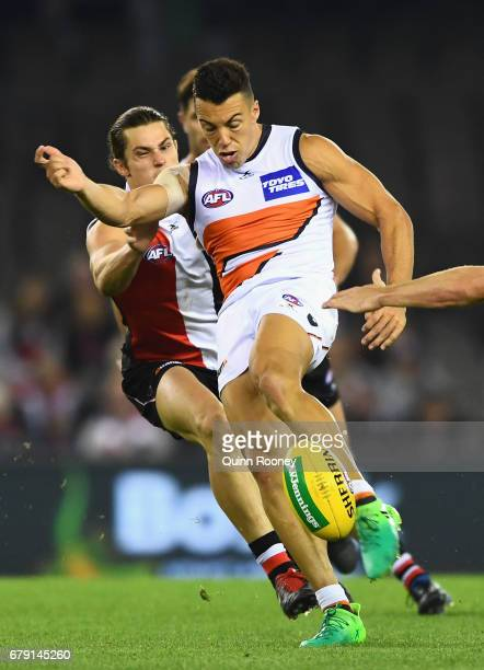 Stephen Coniglio of the Giants kicks whilst being tackled by Jack Steele of the Saints during the round seven AFL match between the St Kilda Saints...