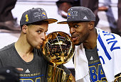 Stephen Curry and Andre Iguodala of the Golden State Warriors celebrate with the Larry O'Brien NBA Championship Trophy after defeating the Cleveland...