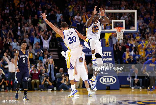 Stephen Curry and Draymond Green of the Golden State Warriors celebrate after Curry made a basket against the Memphis Grizzlies at ORACLE Arena on...