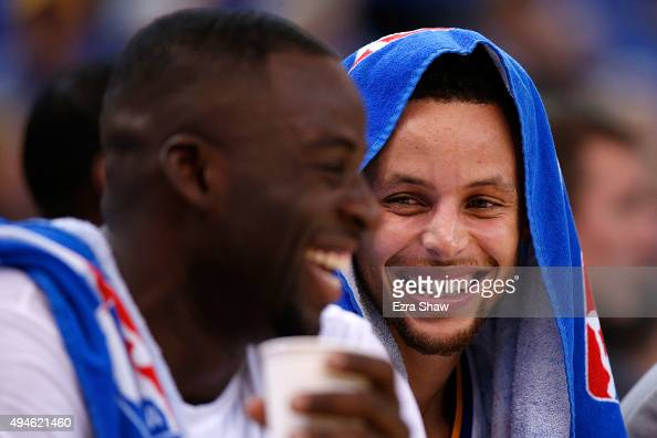 Stephen Curry and Draymond Green of the Golden State Warriors laugh on the bench during the NBA season opener against the New Orleans Pelicans at...