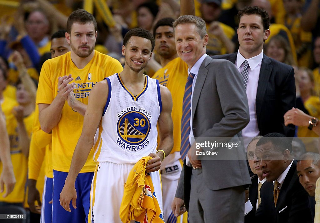 Stephen Curry #30 and head coach Steve Kerr of the Golden State Warriors smile in the fourth quarter while taking on the Houston Rockets during game five of the Western Conference Finals of the 2015 NBA Playoffs at ORACLE Arena on May 27, 2015 in Oakland, California.