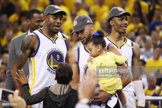 Stephen Curry and his daughter celebrate with Andre Iguodala of the Golden State Warriors after defeating the Cleveland Cavaliers 129120 in Game 5 to...