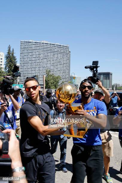 Stephen Curry and Ian Clark of the Golden State Warriors hold up the Larry O'Brien Trophy and run down the street during the Victory Parade and Rally...