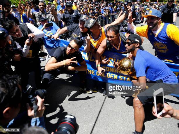 Stephen Curry and Ian Clark of the Golden State Warriors pose for a photo with the Larry O'Brien Trophy and fans during the Victory Parade and Rally...