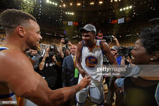 Stephen Curry and Kevin Durant of the Golden State Warriors high five and celebrate with Wanda Durant after winning Game Five of the 2017 NBA Finals...