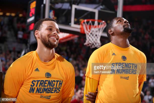 Stephen Curry and Kevin Durant of the Golden State Warriors looks on before the game against the Portland Trail Blazers during Game Four of the...