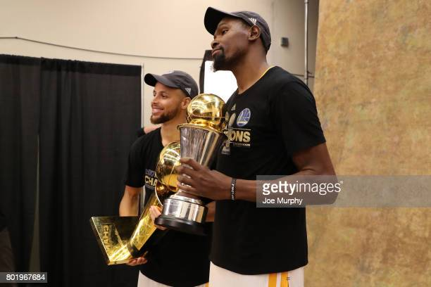 Stephen Curry and Kevin Durant of the Golden State Warriors pose for a photo with the Larry O'Brien Trophy and the Bill Russell Finals MVP Trophy...