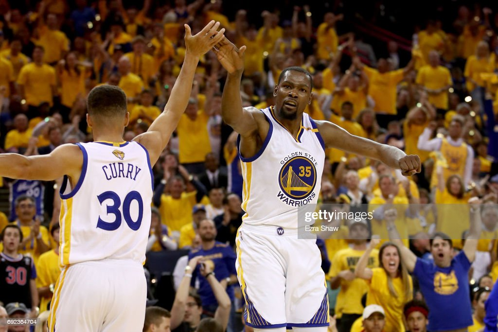 Stephen Curry #30 and Kevin Durant #35 of the Golden State Warriors react to a play against the Cleveland Cavaliers in Game 2 of the 2017 NBA Finals at ORACLE Arena on June 4, 2017 in Oakland, California.