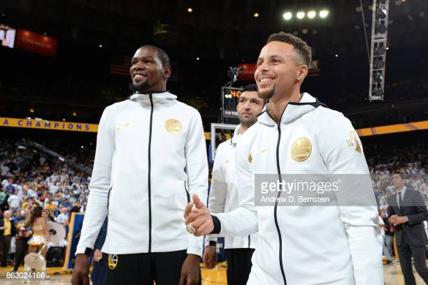 Stephen Curry and Kevin Durant of the Golden State Warriors smile during the championship ring ceremony before the game against the Houston Rockets...