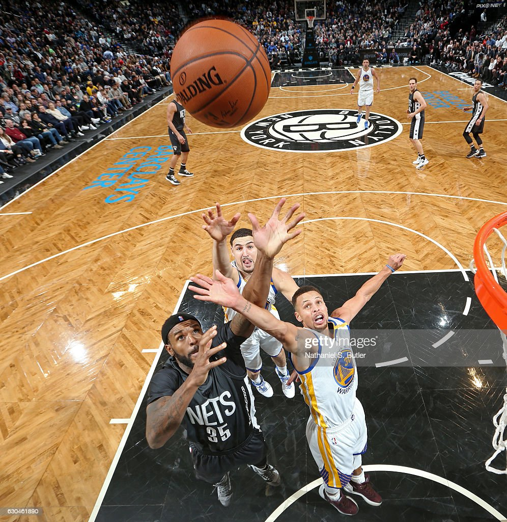 Stephen Curry #30 and Klay Thompson #11 of the Golden State Warriors go up for a rebound against Trevor Booker #35 of the Brooklyn Nets on December 22, 2016 at Barclays Center in Brooklyn, NY.