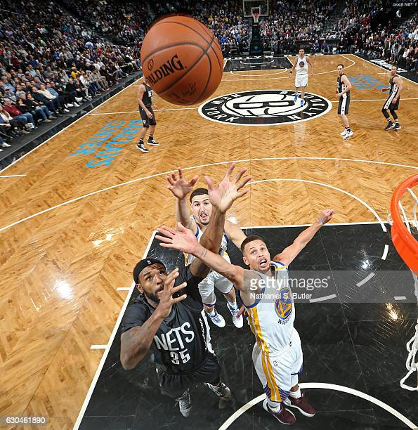 Stephen Curry and Klay Thompson of the Golden State Warriors go up for a rebound against Trevor Booker of the Brooklyn Nets on December 22 2016 at...