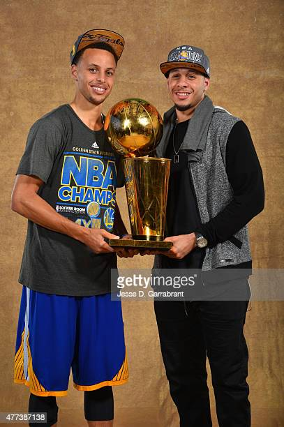 Stephen Curry and Seth Curry of the Golden State Warriors poses for a portrait with the Larry O'Brien trophy after defeating the Cleveland Cavaliers...