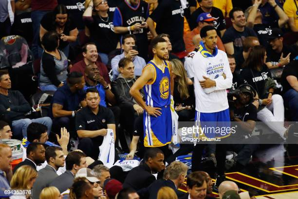 Stephen Curry and Shaun Livingston of the Golden State Warriors look on from the sideline late in the fourth quarter against the Cleveland Cavaliers...
