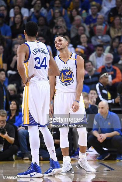 Stephen Curry and Shaun Livingston of the Golden State Warriors talks with each other during a break in the action against the Indiana Pacers in an...