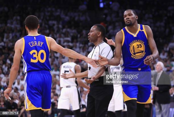 Stephen Curry high fives Kevin Durant of the Golden State Warriors in the first half against the San Antonio Spurs during Game Three of the 2017 NBA...