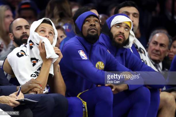 Stephen Curry Kevin Durant and JaVale McGee of the Golden State Warriors look on from the bench in the first half against the Philadelphia 76ers at...