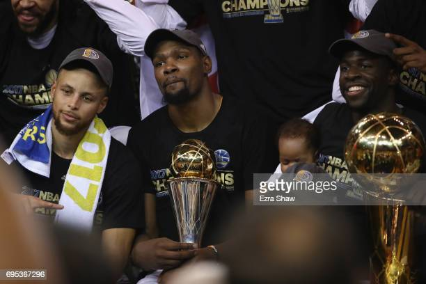Stephen Curry Kevin Durant with the Bill Russell NBA Finals Most Valuable Player Award and Draymond Green of the Golden State Warriors celebrate...