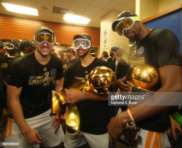 Stephen Curry Klay Thompson and Kevin Durant of the Golden State Warriors celebrate with the Larry O'Brien Trophy and the Bill Russell Finals MVP...