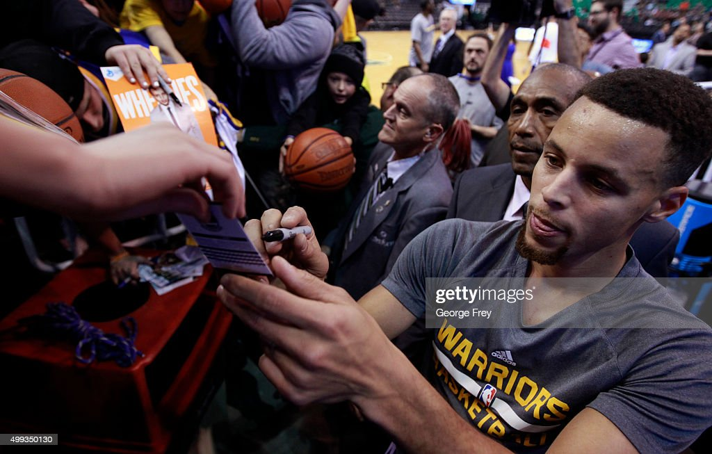Stephen Curry of Golden State Warriors signs fans autographs during warmups before a game against the Utah Jazz at an NBA game November 30 2014 at...