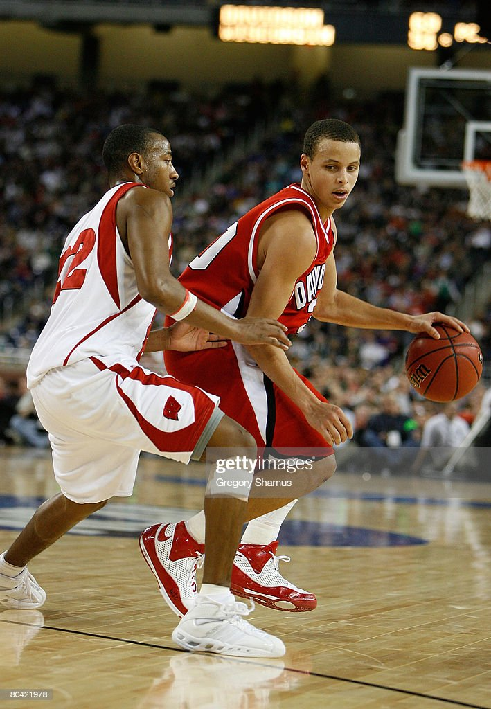 Stephen Curry of the Davidson Wildcats drives against Michael Flowers of the Wisconsin Badgers during the Midwest Regional Semifinal of the 2008 NCAA...