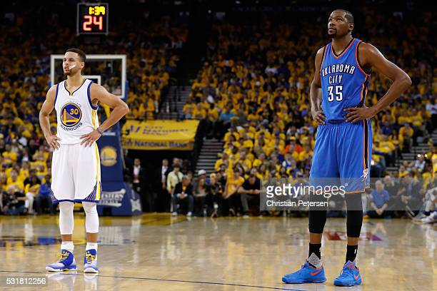 Stephen Curry of the Golden State Warriors and Kevin Durant of the Oklahoma City Thunder stand on the court during game one of the NBA Western...