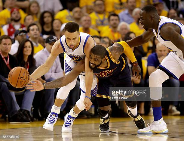 Stephen Curry of the Golden State Warriors and Kyrie Irving of the Cleveland Cavaliers go after the ball in the first half in Game 1 of the 2016 NBA...
