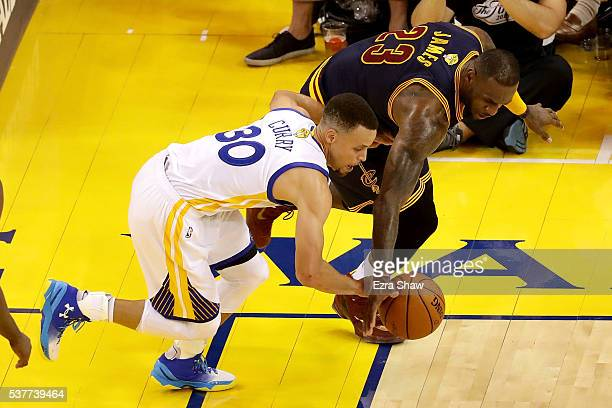 Stephen Curry of the Golden State Warriors and LeBron James of the Cleveland Cavaliers go after a loose ball in the first half in Game 1 of the 2016...
