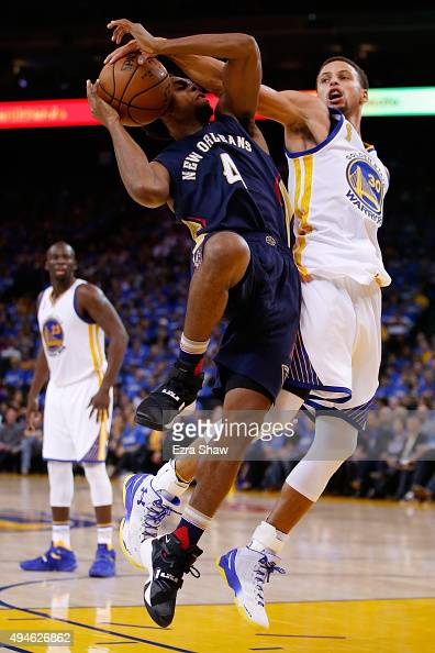 Stephen Curry of the Golden State Warriors blocks a shot by Ish Smith of the New Orleans Pelicans during the NBA season opener at ORACLE Arena on...