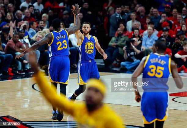 Stephen Curry of the Golden State Warriors celebrates a three point shot with Draymond Green against the Portland Trail Blazers during Game Four of...