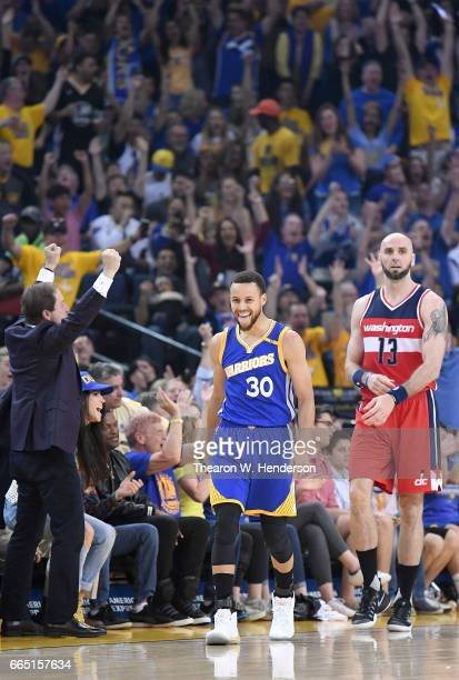 Stephen Curry of the Golden State Warriors celebrates after making a threepoint shot over Marcin Gortat of the Washington Wizards during an NBA...