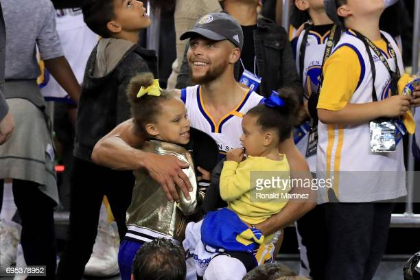 Stephen Curry of the Golden State Warriors celebrates holding his daughters Riley and Ryan after defeating the Cleveland Cavaliers 129120 in Game 5...
