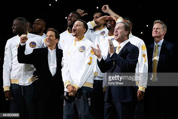 Stephen Curry of the Golden State Warriors celebrates with owners Peter Guber and Joe Lacob as their 2015 championship banner is unveiled prior to...