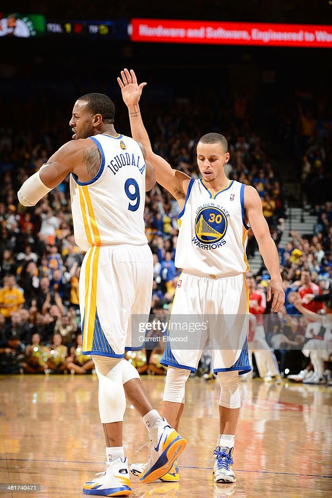 Stephen Curry #30 of the Golden State Warriors celebrates with teammate <a gi-track='captionPersonalityLinkClicked' href=/galleries/search?phrase=Andre+Iguodala&family=editorial&specificpeople=201980 ng-click='$event.stopPropagation()'>Andre Iguodala</a> #9 during the game against the Boston Celtics on January 10, 2014 at Oracle Arena in Oakland, California.
