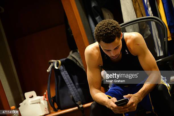 Stephen Curry of the Golden State Warriors checks his smartphone before the game against the New Orleans Pelicans for Game Four of the Western...